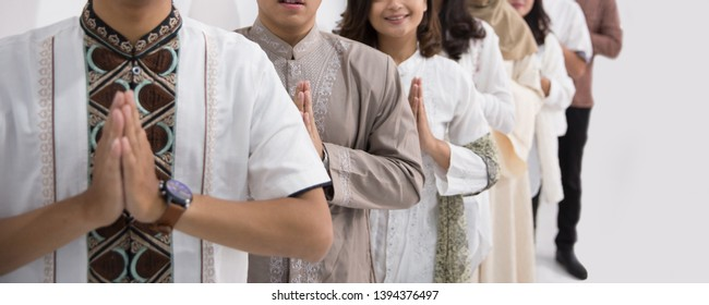Group of muslim asian men and women smiling and greeting. embracing each other during eid mubarak celebration