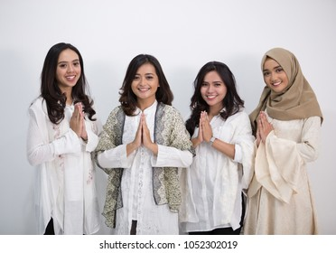 Group of muslim asian women smiling and greeting. embracing each other during eid mubarak celebration