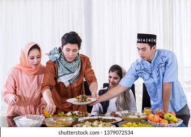 Group of Muslim people eating foods during breaks the fast together in the dining room. Shot at home