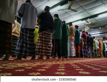 A group of Muslim people pray in a mosque. Muslims face to the direction of Mecca during prayer (salah).