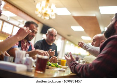 Group of Muslim people in restaurant enjoying Middle Eastern food. Selective focus