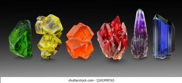 A group of natural gem crystals arranged in a rainbow, including peridot , sulphur, spessartine garnet, rhodochrosite, amethyst and tanzanite.