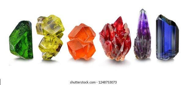 A group of natural gem crystals arranged in a rainbow, including peridot , sulphur, spessartine garnet, rhodochrosite, amethyst and tanzanite.