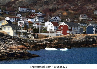 Group of new vacation homes built on the shore of Brigus Cove in Conception (Brigus) Bay Newfoundland, Canada. Two ice blocks separated from bigger Iceberg reached to the Coast Line of Brigus Cove