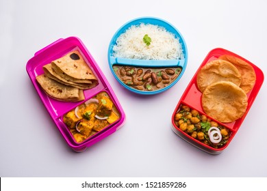Group of North Indian Food in Tiffin , Lunch Box includes Rajma or Razma Chawal, paneer Butter Masala Roti or Paratha and choley puri / Poori / Bhature, selective focus