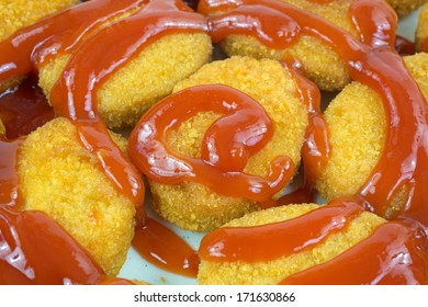 A group of nugget size breaded white chicken  drizzled with a spicy ketchup sauce.