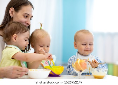 Group of nursery babies eating healthy food with babysitter help. Lunch break in creche. Time to eat in day care