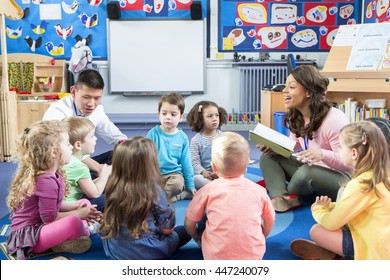 Group of nursery children sitting on the floor in their classroom with their teachers. The female teacher is reading from a book.