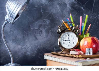 Group of Objects Close up Concept Back To School Alarm Clock Color Pencil Apple Notebook Lamp Stationery Black Blackboard Background Behind. Design Copy Space Education Supplies