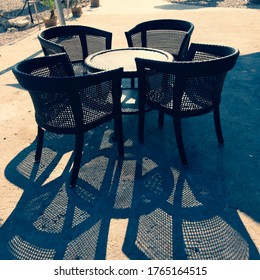 A group of objects, four black chairs and one round table on the cafe terrace on a sunny day