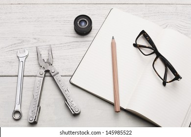 Group of objects and a plain textbook on white hardwood table, Studio shot.