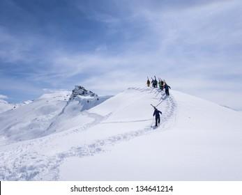 Group of off piste skiers walking on ridge.