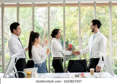Group at Office Business Woman Celebrating success. The Female Employees are Happy to Receive the Trophy and Shouted with Joy from Winning a Outstanding Employee Award.