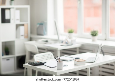Group of office supplies on desk with chair near by on background of another workplace by window
