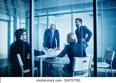 Group of office workers listening to their colleague at meeting