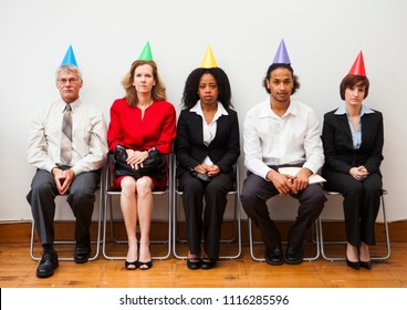 A group of office workers looking bored or disinterested while wearing party hats. Humorous business concept.