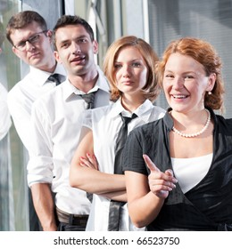 Group of office workers posing for camera in office building. Two women and two men happy smilling for camera. Red-haired lady pointing out.