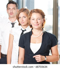 Group of office workers posing with red-haired manager woman in front. Office worker posing in office building: two women and one man looking at camera.