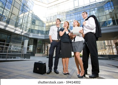 Group of office workers staying in front of modern business building in full length. Serious people posing outdoors after hard working day.