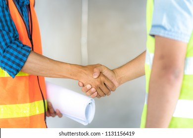 Group of officer teamwork is happy and shake hands to celebrate in success of finish in job planning about home building construction project