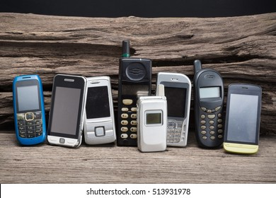 group of old and obsolete mobile phone on old wood