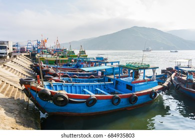 Group of old wooden fish boats in harbor/Qui Nhon, Vietnam - March 26 2017: These people were sitting in their ship. At the morning, Qui Nhon fish market, Qui Nhon city, Vietnam