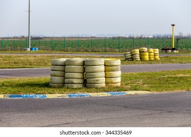 Group of old yellow painted tires used for protection on a racing track