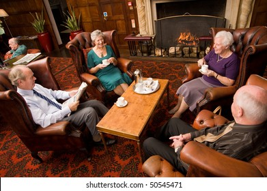 A group of older senior friends enjoying tea and talking in hotel lounge area