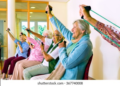 Group of older women seated in chairs using stretching bands for physical fitness class
