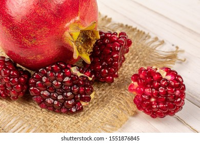 Group of one whole four pieces of fresh red pomegranate on natural sackcloth on white wood