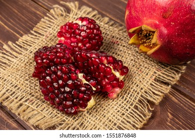 Group of one whole four pieces of fresh red pomegranate on natural sackcloth on brown wood