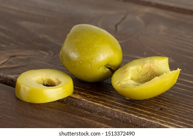 Group of one whole one half one slice of pitted green olive on brown wood