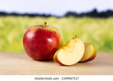 Group of one whole two slices of fresh red apple james grieve variety with green wheat field in background