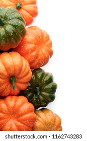 Group of orange and green pumpkins, closeup shot, white background, seasonal design element
