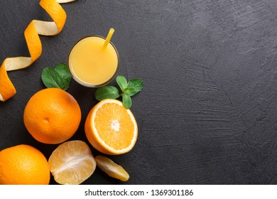 A group of oranges and a glass of juice on a dark background.