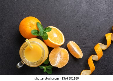 A group of oranges and a jar of juice on a dark background.