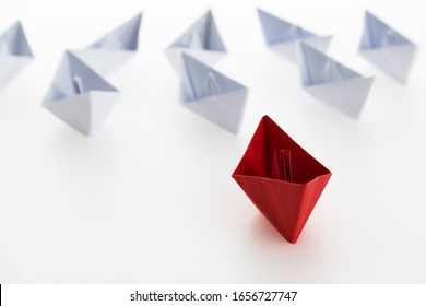 Group of origami boats on white background.