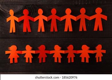 Group of paper doll holding hands. Teamwork concept paper craft. Orange dolls on black wooden background