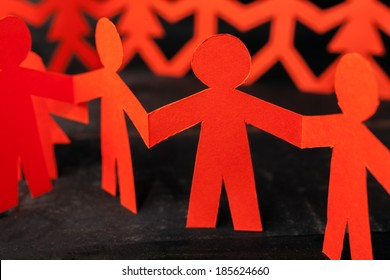 Group of paper doll holding hands. Teamwork concept paper craft. Orange dolls on black wooden background