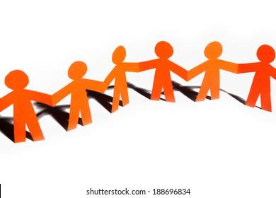 Group of paper doll holding hands. Teamwork concept paper craft. Orange dolls on white background