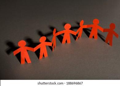 Group of paper doll holding hands. Teamwork concept paper craft. Orange dolls on gray background