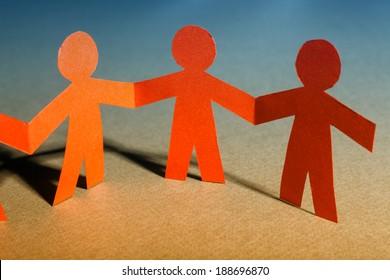 Group of paper doll holding hands. Teamwork concept paper craft. Orange dolls on orange-blue background