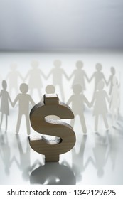 Group of paper people holding hands in front of big dollar sign. Consumerism, economy concept.