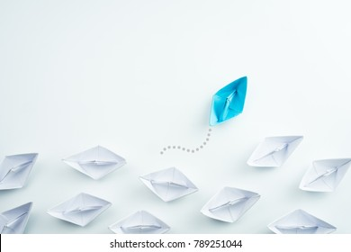 Group of paper ship in one direction and one individual pointing in different way. innovative solution for business concept.