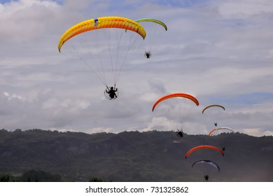 group of paramotor flying in the sky against the background of clouds