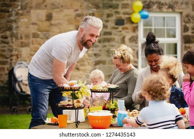 Group of parents and children sitting outdoors and enjoying a easter garden party. They are enjoying food and drink.