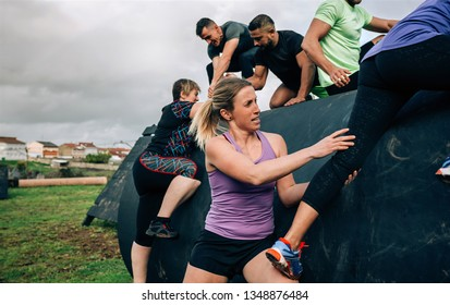 Group of participants in an obstacle course climbing a drum helped by their teammates