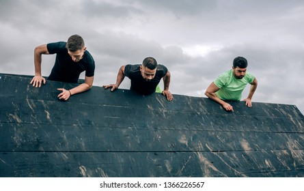 Group of participants in an obstacle course climbing an inverted wall