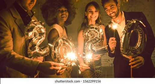 Group of party people celebrating the arrival of 2020, men and women looking into camera