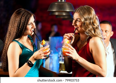 Group of party people with cocktails in a bar or club having fun